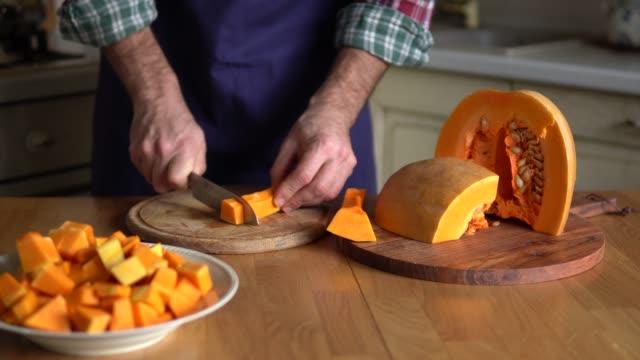 vidéos et rushes de l'homme coupe la citrouille se préparant pour le dîner de thanksgiving - citrouille