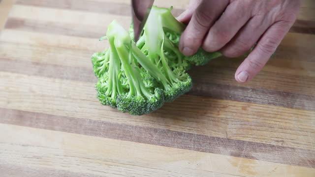 man cuts up broccoli - broccolo video stock e b–roll