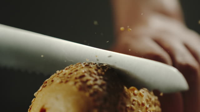 CLOSE UP: Man Cutting A Crispy Baguette With Crumbs On Wooden Board - slow motion