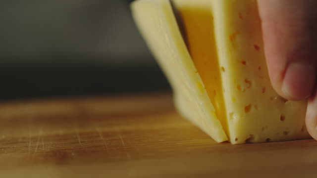 SLOW MOTION: Man Cutting A Slice Of Cheese On Wooden Board SLOW MOTION: Man Cutting A Slice Of Cheese On Wooden Board cheese stock videos & royalty-free footage