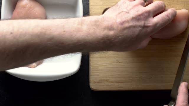 vídeos de stock, filmes e b-roll de ver os filetes de frango de corte homem no topo de uma placa de madeira - cru