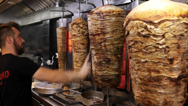 man cutting gyro in fast food restaurant - spiedino video stock e b–roll