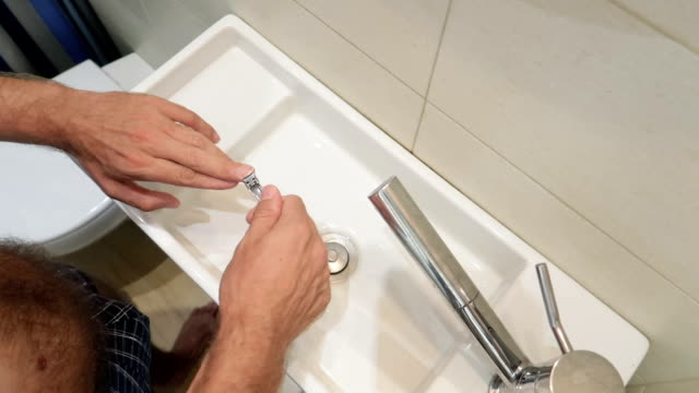 man cutting his hand's nails in a bathroom in slow motion - nail work tool stock videos & royalty-free footage