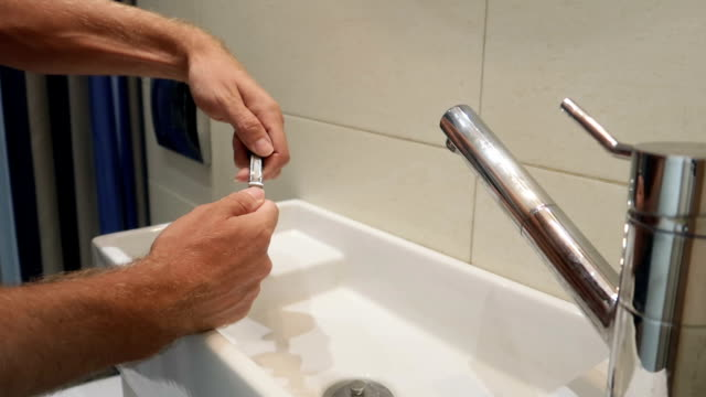 man cutting his hand's  nails in a bathroom in slow motion - ноготь на руке стоковые видео и кадры b-roll