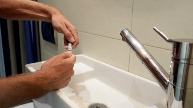 man schneidet seine hand nägel in einem badezimmer in zeitlupe - fingernagel stock-videos und b-roll-filmmaterial