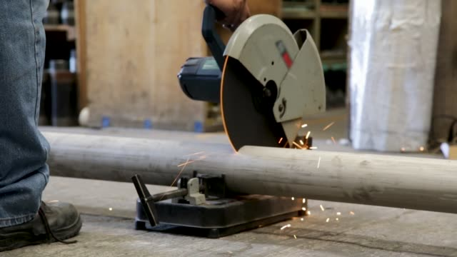 Man cutting pipe with machinery