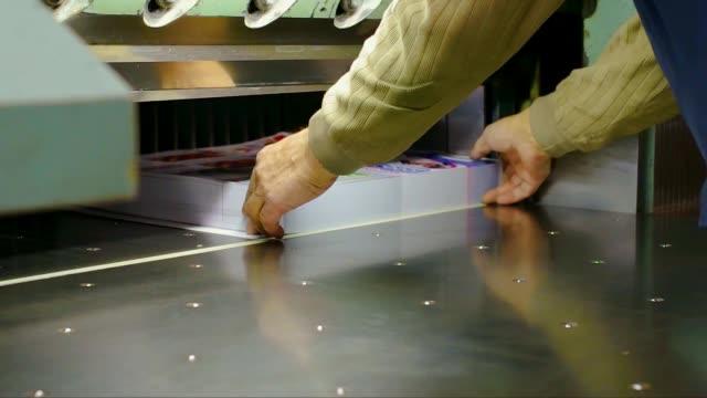 vidéos et rushes de homme coupe production imprimée sur une guillotine de papier - presse