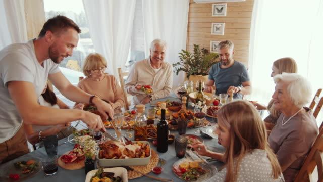 vídeos y material grabado en eventos de stock de hombre cortando pavo asado para la familia en la cena de acción de gracias - thanksgiving turkey