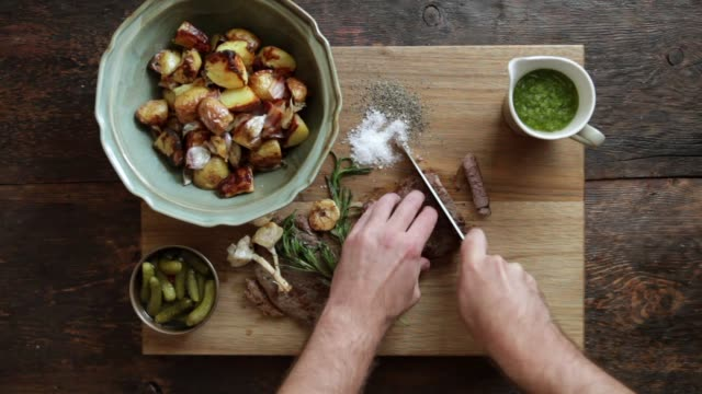 vídeos de stock e filmes b-roll de man cutting steak with fresh herb sauce and grilled vegetables - beef angus