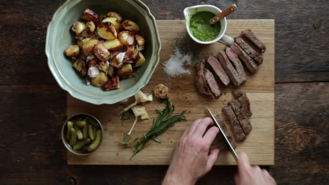 Man cutting steak with fresh herb sauce and grilled vegetables