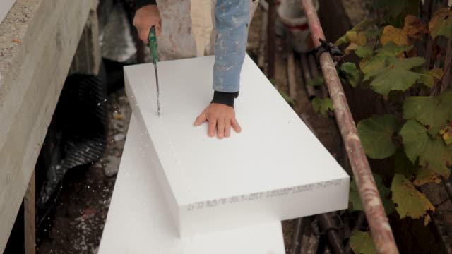 man cutting styrofoam insulation board for energy saving on exterior wall of house - poliuretano polimero video stock e b–roll