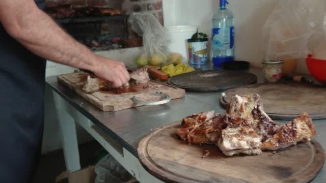 man cutting the argentinian barbecue pork serving in a plate - płyta do pieczenia filmów i materiałów b-roll