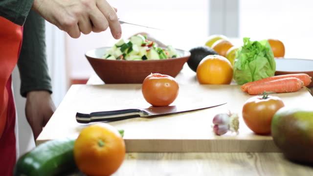 man cutting tomato on wooden cutting board video
