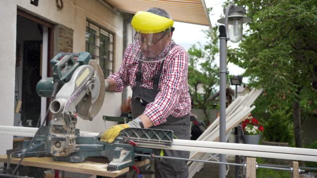 mann schneidet holz in seiner heimwerkstatt - kreissäge stock-videos und b-roll-filmmaterial