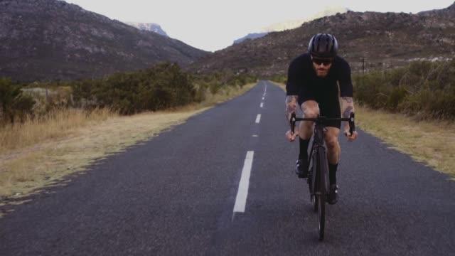 man cycling fast on long flat road - ciclismo su strada video stock e b–roll