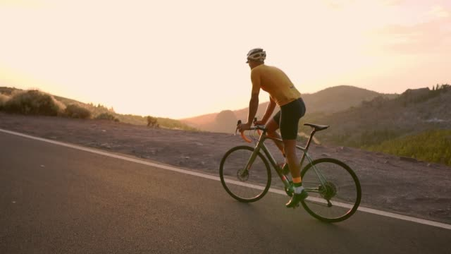 Man cycling on road bike outdoor exercise on an empty road in the morning .Extreme sport concept. slow motion