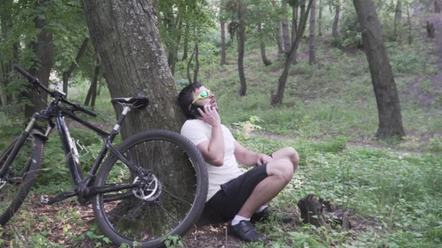 vídeos de stock e filmes b-roll de man cyclist athlete chest injury pain. male suffers from painful chest or symptoms heart disease while cycling in forest asks for help, calls 911 ambulance. healthcare, insurance and medicine theme - miocárdio