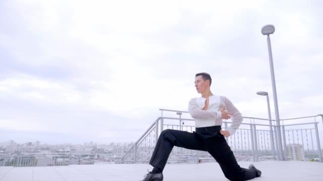 都市の背景に美しい男踊り。 - バレエ点の映像素材/bロール