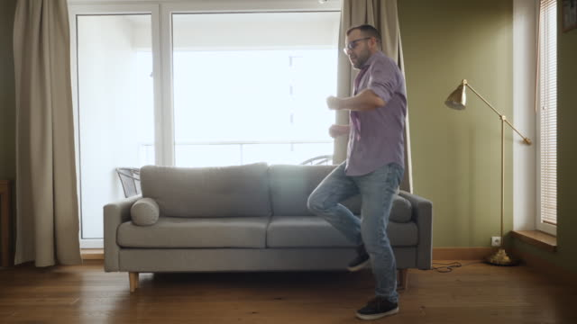 man dancing at home living room, fun celebrating funny viral dance freedom weekend. happy young guy enjoying shuffle dance, having fun party. joyful man dancing cheerful in living room. happy people. - tiktok стоковые видео и кадры b-roll