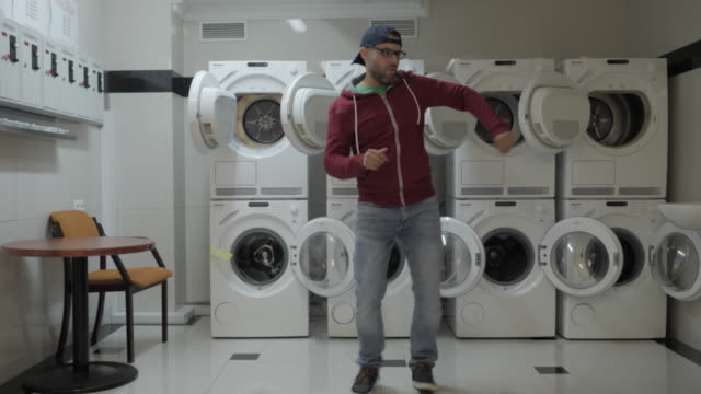 man dancing viral dance and have fun in the laundry room. happy guy enjoying dance, having fun together, party. joyful man with beard in cap and glasses dancing cheerful in laundry room. slow motion. - tiktok стоковые видео и кадры b-roll