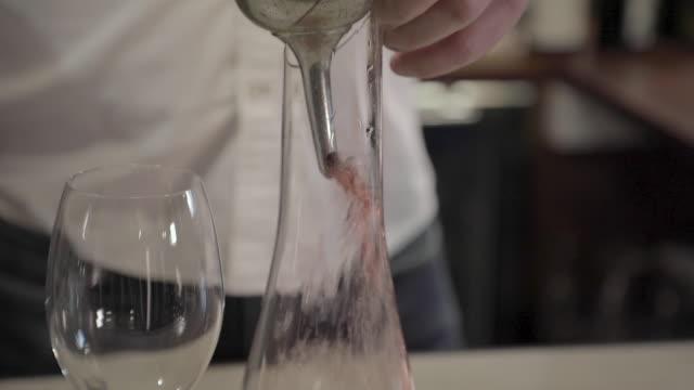 vidéos et rushes de un homme décante le vin rouge dans une carafe - entonnoir