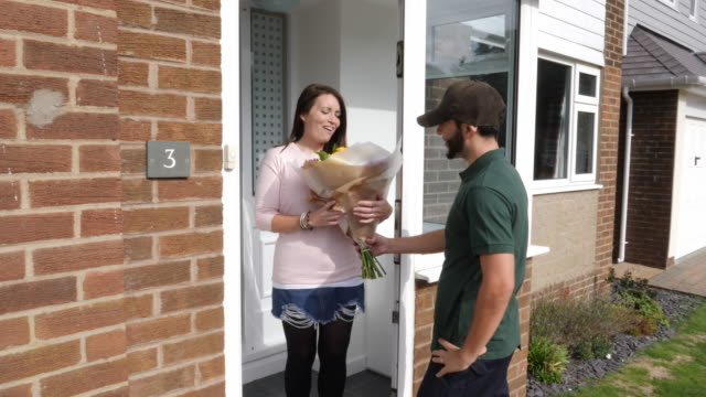 4k: man delivers bouquet of flowers to a woman at her house - front door (outdoors) - bouquet video stock e b–roll