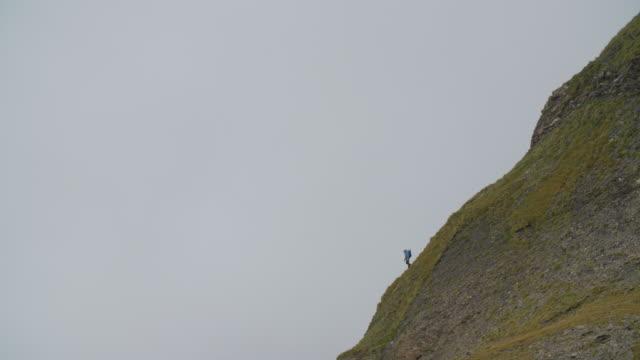 vídeos de stock e filmes b-roll de a man descending a steep mountain in cloudy conditions. - weatherman