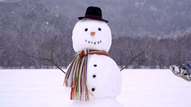 Man destroying a snowman Young man jump into a snowman and destroys it snowman stock videos & royalty-free footage