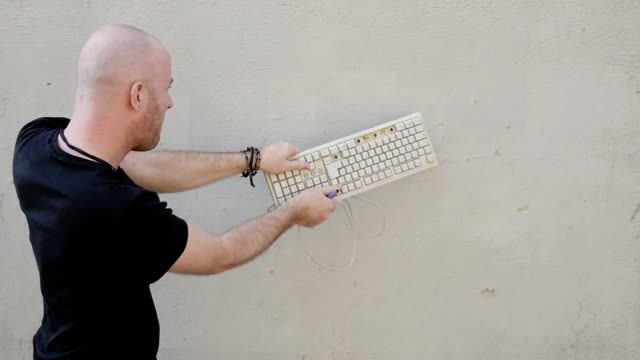 man destroying keyboard against a wall: violence, outburst, anger video