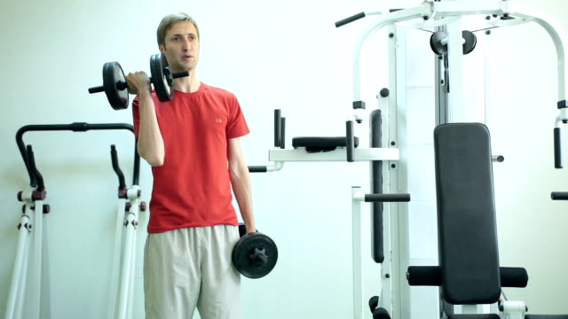 Man develops biceps with the help of dumbbells. video