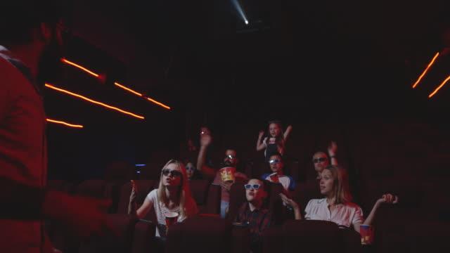 man disturbing fellow moviegoers in cinema - spoiler filmów i materiałów b-roll