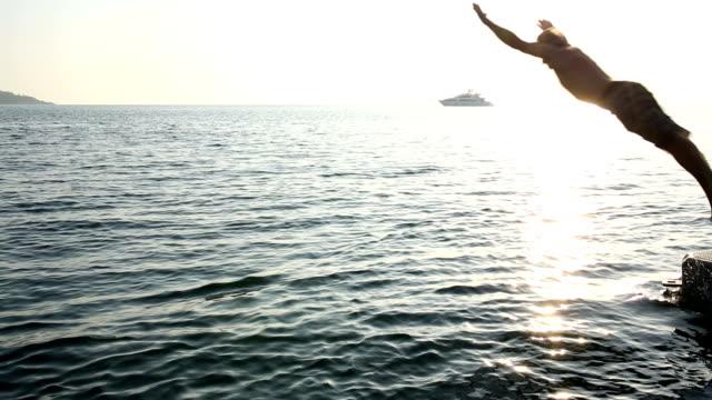Hombre dives en mar, amanecer desde el muelle - vídeo