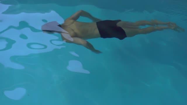vídeos de stock e filmes b-roll de man dives into the pool, swims - swim arms