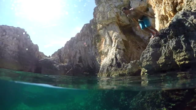 slow motion underwater: man diving headfirst into ocean water on sunny vacation - sky diving video stock e b–roll