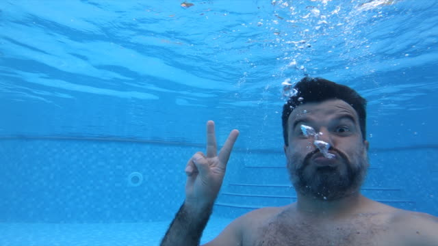 man diving in pool - vacanze video stock e b–roll