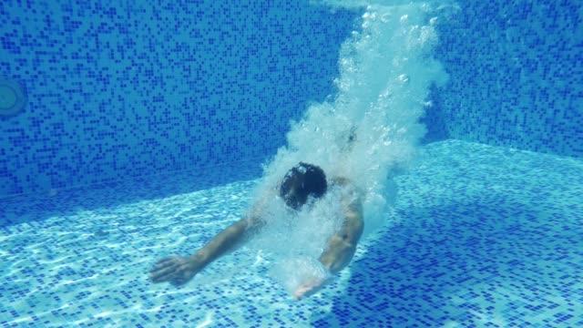 vídeos de stock e filmes b-roll de man diving into swimming pool - jump pool, swimmer