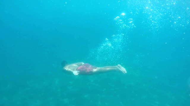 Man diving to sea bottom video