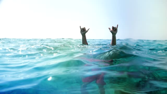 Man diving underwater and doing rock and roll hand gesture video