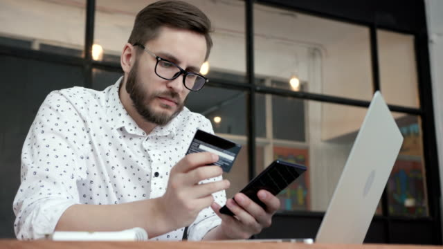 Man do payment online by phone credit bank card One young male person in glasses sit in workspace, hold cellphone and looking shop on line. Consumer pay by contactless debit bankcard. Commercial concept of buyer use the currency by telephone electronics store stock videos & royalty-free footage