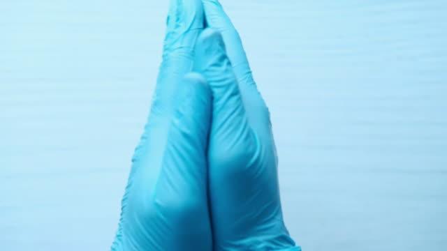 vidéos et rushes de médecin homme porte des gants médicaux, fermer - bras humain