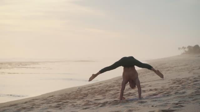 man does headstand during training at beach, standing on arms, then sits on twine - ludzka kończyna filmów i materiałów b-roll