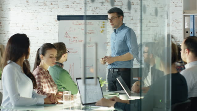 Man Does Whiteboard Presentation to His Creative Office Staff. Coworkers Sit at the Big Glass Table with Open Laptops, Taking Notes. Office is Stylish and Bright.