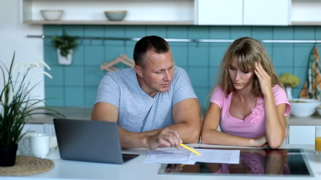 Man doing accounts together with his wife at home video
