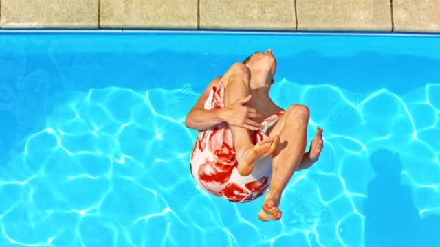 SLO MO CS Man doing backflip into the pool Slow motion medium crane shot of a man jumping a backflip into the pool. jumping stock videos & royalty-free footage
