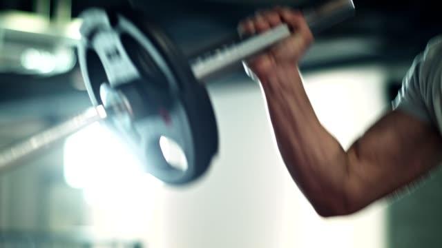 vídeos de stock e filmes b-roll de man doing barbell exercise in the gym - peso equipamento para exercícios