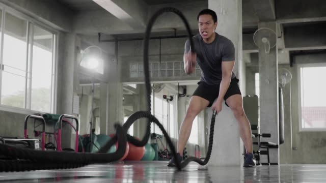 (slow motion) man doing battle ropes exercise in a fitness gym. - irriducibilità video stock e b–roll