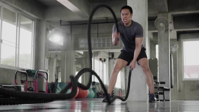 (slow motion) man doing battle ropes exercise in a fitness gym. - napinać mięśnie filmów i materiałów b-roll