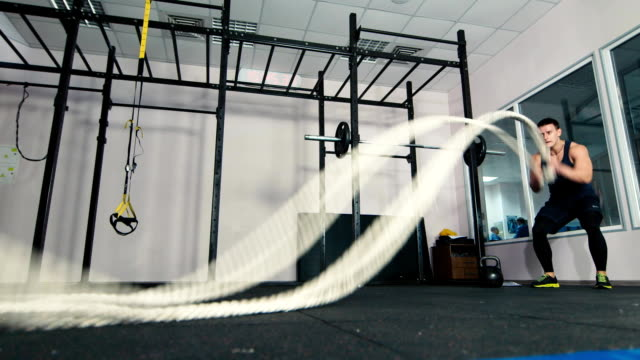 Man doing battling rope exercise at the gym