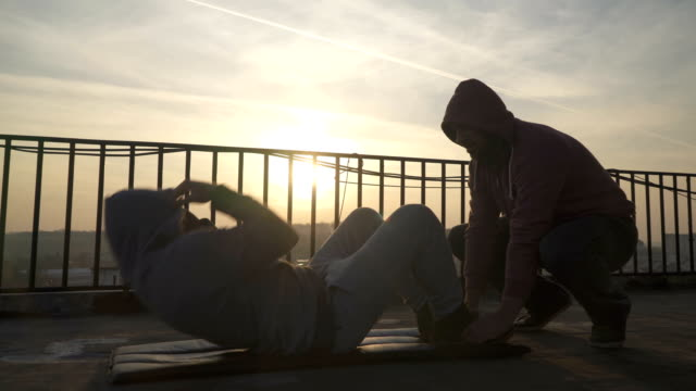 man doing crunches on terrace in beautiful sunset, trainer holding his legs, sportsman practicing, power training, strong guy hard exercising, strength exercises, workout, handheld, sunny day. - man city exercise abs video stock e b–roll