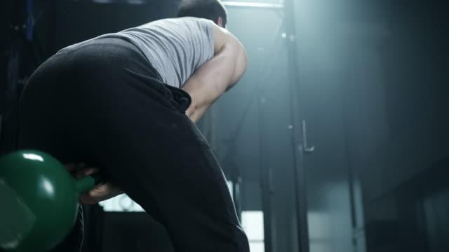 mann tut übung mit keetlebell im fitness-studio - kugelhantel stock-videos und b-roll-filmmaterial